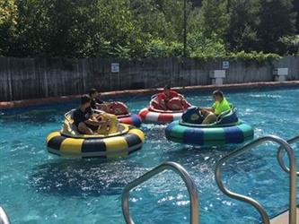 Students in large inner tubes floating in a pool