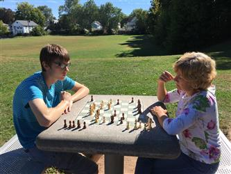 2 students playing chest in a park