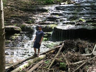 A student standing in front of a waterfall