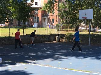 3 students playing basketball