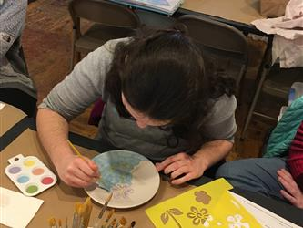 A student painting a plate