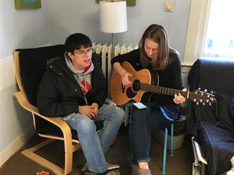 A student playing a guitar for another student