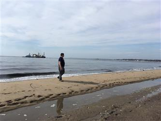 A student walking on a beach