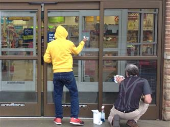 2 students washing the glass door of a store