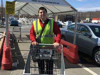 A student wearing a reflective vest pushing a shopping cart